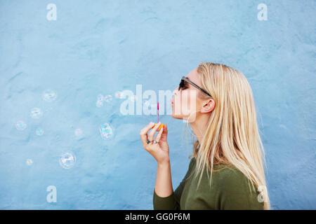 Richtungskontrolle Blick des jungen schönen Frau Seifenblasen vor blauem Hintergrund. Junge, blonde Frau Spaß zu haben. Stockfoto