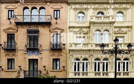 Detail der angrenzenden Gebäude mit zwei klassischen architektonischen Stilrichtungen in Sevilla, Spanien - Stockfoto