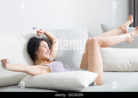 Junge Chinesin, die entspannend auf sofa - Stockfoto