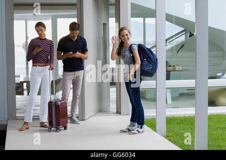 Teenager Mädchen winken Hand mit ihren Gästen auf Tür stehen - Stockfoto