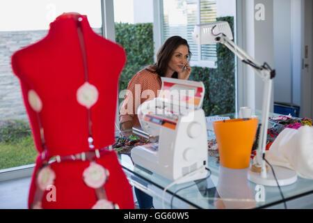 Glücklich Kleid Designer telefonieren mit Handy - Stockfoto