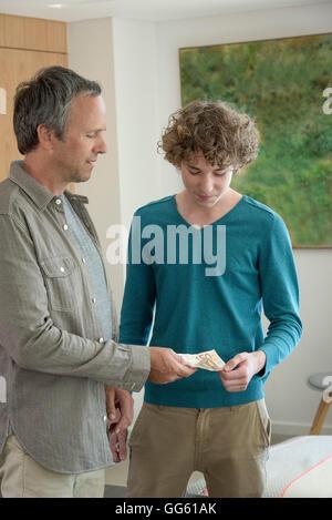 Vater und Sohn im Teenageralter Taschengeld - Stockfoto