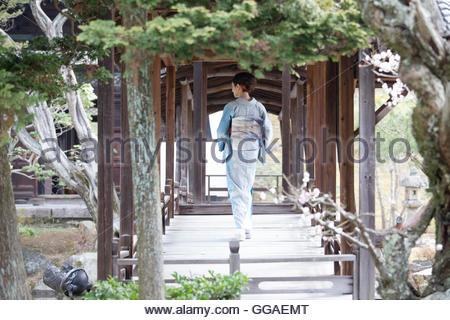 Junge Japanerin Kimono zu Fuß auf der Holzbrücke - Stockfoto