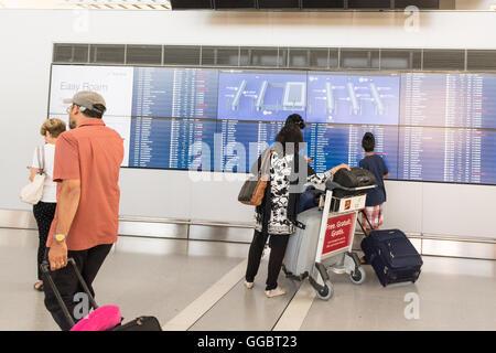 Toronto Pearson International Airport - Passagier-Familie betrachten Anzeigentafel im Terminal 1 - Stockfoto