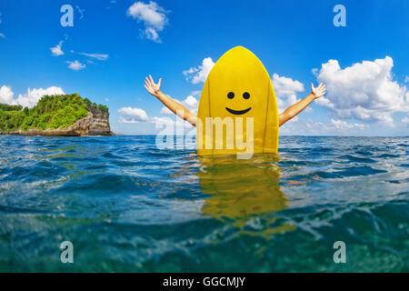 Glückliche junge Surferin auf gelben Surfbrett mit Smiley-Gesicht sitzen und hat Spaß. Gesunder Lebensstil, Menschen - Stockfoto