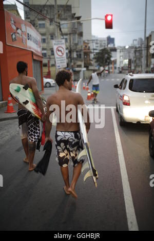 Surfer am Abend vom Strand kommend auf Avenida Oceanica, Barra, Salvador de Bahia, Bahia, Brasilien - Stockfoto