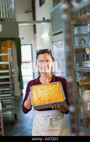 Kaukasische Frau zeigt Kuchen in Bäckerei Pfanne - Stockfoto