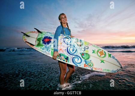Kaukasische Frau mit Surfbrett am Strand - Stockfoto