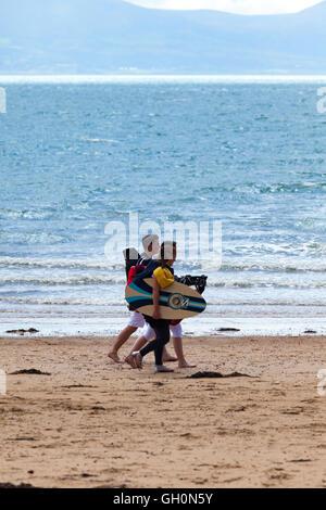 Freunde entlang Newborough Strand, Anglesey, Wales, UK mit ihre Surf-Ausrüstung - Stockfoto
