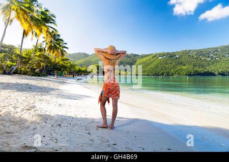 Frau im Sarong und Hut stehend an einem tropischen Strand mit beiden Händen hinter ihr, Magens Bay, St. Thomas, - Stockfoto
