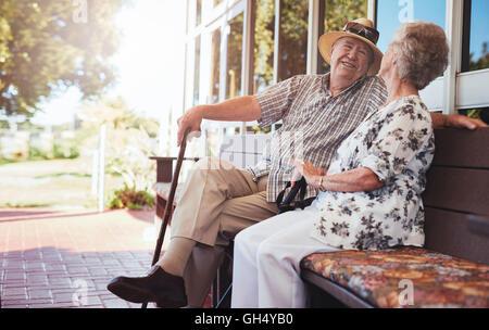 Älteres Paar mit einem Chat beim Sitzen auf einer Bank außerhalb der eigenen Wohnung zu lieben. Gerne älteres Paar - Stockfoto