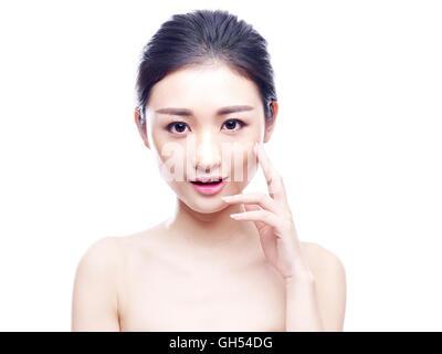 Studio-Porträt der jungen und schönen Asiatin hand aufs Kinn, Blick in die Kamera, isoliert auf weißem Hintergrund. - Stockfoto