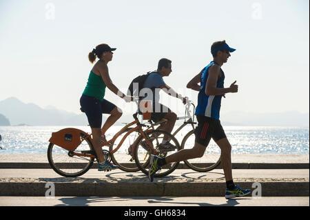 RIO DE JANEIRO - 3. April 2016: Jogger und Radfahrer Anteil der Radweg direkt am Copacabana Strand Avenida Atlântica - Stockfoto