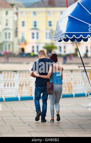 Einen warmen Sommerabend in Llandudno mit Besucher genießen den Abend im Resort. Ein junges Paar Arm in Arm spazieren - Stockfoto