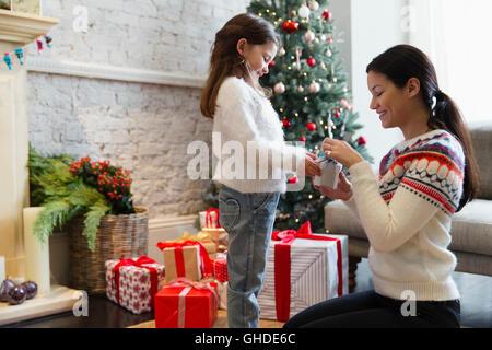 Mutter und Tochter Weihnachtsgeschenk im Wohnzimmer öffnen - Stockfoto