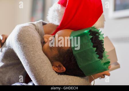 Liebevolle paar Papierkrone und Santa Hut umarmt - Stockfoto
