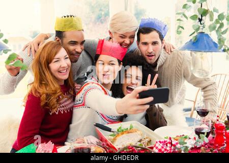 Freunde tragen Papier Kronen nehmen Selfie am Weihnachtsessen - Stockfoto