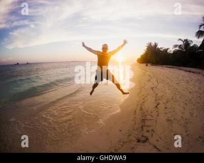 Porträt des ausgelassenen Menschen springen auf tropischen Strand bei Sonnenuntergang - Stockfoto