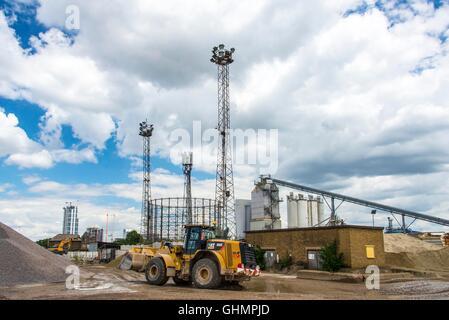 Bagger bewegen Kies Aggregate in Lagerung und Dimensionierung der Anlage von Thames Path mit Silos Fabrik Lichter - Stockfoto