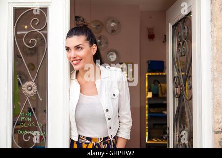 Porträt der jungen Frau in der Tür des Restaurants - Stockfoto