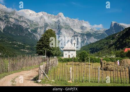Blick über das Dorf Theth mit der Schindel überdachte Kirche und die albanischen Alpen im Hintergrund, Nordalbanien. - Stockfoto