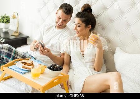Junges Liebespaar im Bett frühstücken - Stockfoto