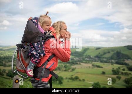 Junge glückliche Mutter halten wenig Reisende auf Rückseite - Babymädchen in Rucksack Reisen Abenteuer, Wandern - Stockfoto