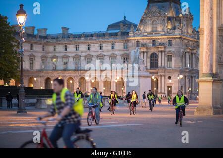 eine Tour mit dem Bike-Gruppe übergeben den Arc de Triomphe du Carrousel & Palais du Louvre in der Abenddämmerung, - Stockfoto