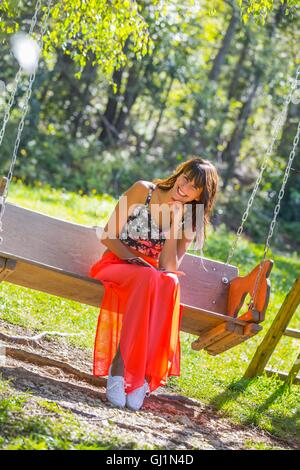 Gutes Mädchen im Freien sitzen auf Holz schaukeln Sitzbank in Park lächelnd Vorderansicht lesen Buch langes Kleid - Stockfoto