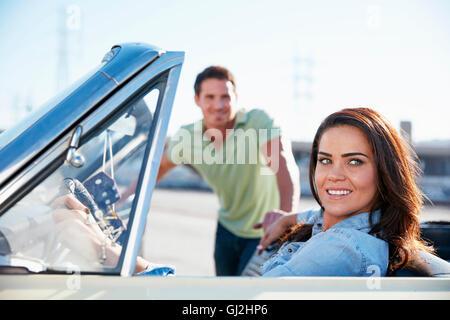 Frau im Cabrio, Mann steht neben dem Auto - Stockfoto