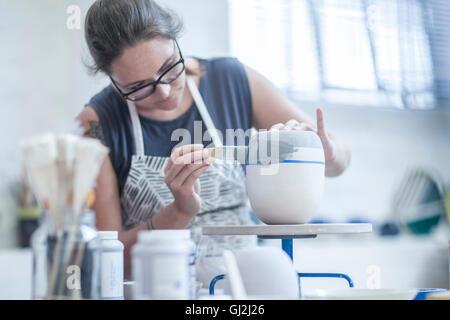Weibliche Potter Malerei Keramikglasur auf Vase in Werkstatt - Stockfoto