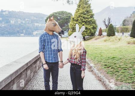 Paar mit Pferd und Kaninchen Masken Hand in Hand, Comer See, Italien - Stockfoto