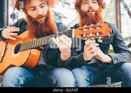 Junge männliche Hipster Zwillinge mit roten Bärten sitzen Gitarre spielen - Stockfoto