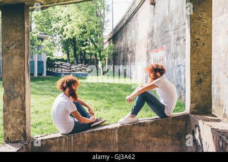 Junge männliche Hipster Zwillinge mit roten Bärten sitzen auf Wand - Stockfoto