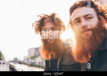 Junge männliche Hipster Zwillinge mit roten Haaren und Bärten am Kanal Wasser - Stockfoto