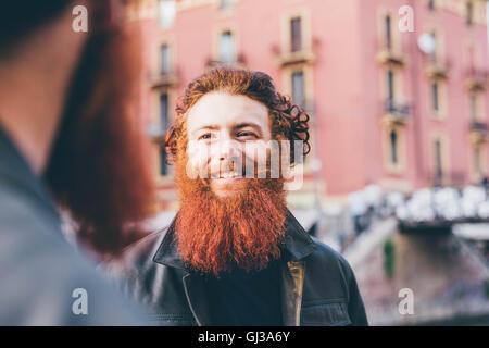 Junge männliche Hipster Zwillinge mit roten Haaren und Bärten reden auf Straße - Stockfoto