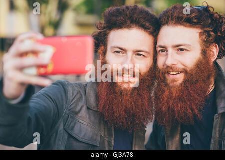 Junge männliche Hipster Zwillinge mit roten Haaren und Bart unter Smartphone selfie - Stockfoto