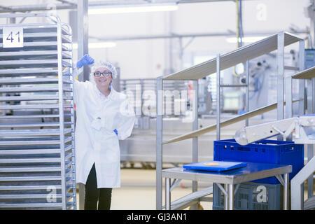 Fabrikarbeiter, Haarnetz Blick auf Kamera Lächeln auf den Lippen tragen - Stockfoto