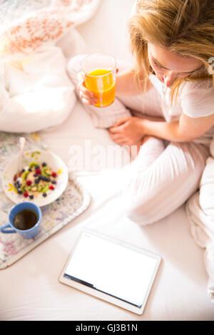 Draufsicht der jungen Frau auf Bett und Las digital-Tablette morgens - Stockfoto