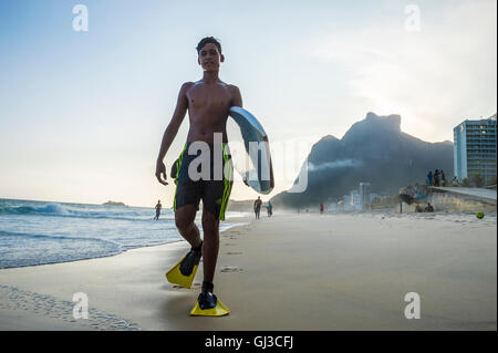 RIO DE JANEIRO - 8. März 2016: Junge Carioca brasilianischen Bodyboarder betritt die Wellen am Strand von São Conrado. - Stockfoto