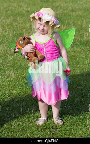 Burley, Hampshire, UK. 13. August 2016. Junges Mädchen gekleidet als Fee hält Spielzeughund in einer Hand und Zauberstab - Stockfoto