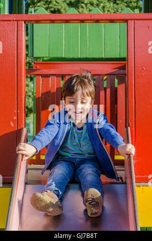 Ein kleiner Junge spielt auf einer Folie in einen Kinderspielplatz. - Stockfoto