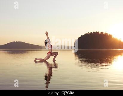Junge Frau praktizieren Hatha Yoga auf einer schwimmenden Plattform im Wasser auf dem See bei nebligen Sonnenaufgang - Stockfoto