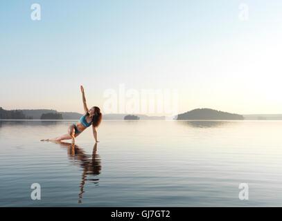 Junge Frau praktizieren Hatha Yoga auf einer schwimmenden Plattform im Wasser auf dem See in den frühen Morgenstunden. - Stockfoto