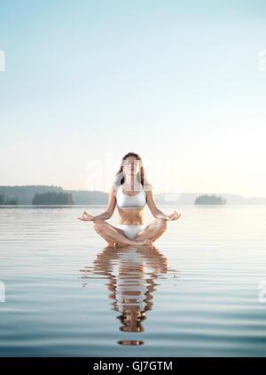 Junge Frau in weißen Badeanzug zu meditieren. Praxis der Meditation auf einer schwimmenden Plattform in ruhigem - Stockfoto