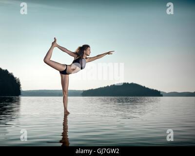 Junge Frau praktizieren Hatha Yoga auf einer schwimmenden Plattform im Wasser auf dem See bei Sonnenaufgang am Morgen. - Stockfoto