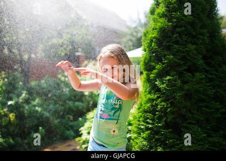 Vorschulkind niedliche Mädchen spielen mit Garten Sprinkler. Sommer im freien Wasserspaß im Hinterhof. - Stockfoto