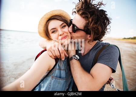 Glückliches junges Paar küssen und unter Selfie im freien - Stockfoto