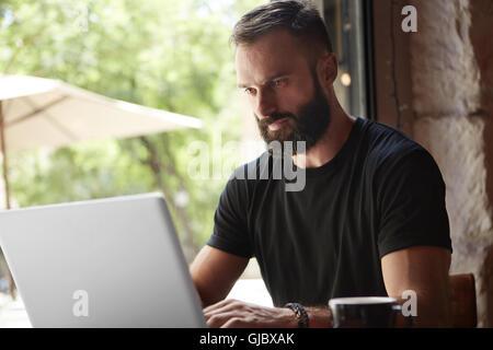Bärtigen Mann tragen schwarze Tshirt Laptop Holztisch Urban Cafe.Young Manager arbeiten Notebook modernes Interior Design Loft Place.Coworking Business Startup.Color Prozessfilter arbeiten konzentriert.