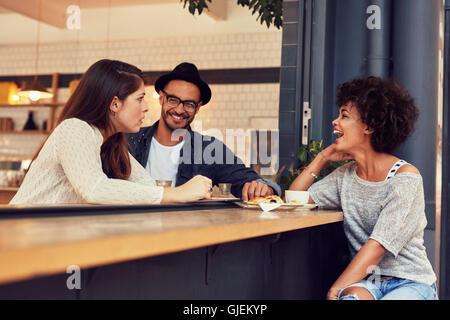 Porträt einer jungen Gruppe von Freunden in einem Café im Gespräch. Junger Mann und Frauen sitzen im Café-Tisch - Stockfoto